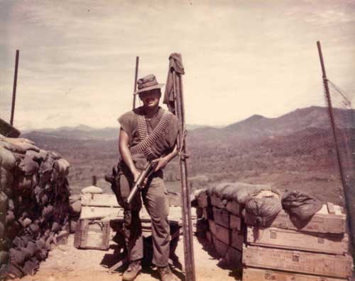 Charley Trujillo holding a grenade launcher in Viet Nam in 1970