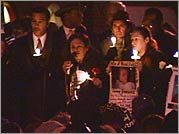 Iris Baez speaks at a candlelight memorial for her son Anthony.