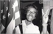 Chisholm poses with flag making victory sign