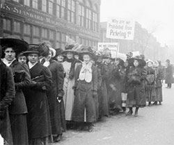 Image of a parade of women during the garment workers' strike in Chicago, Illinois. Some women are carrying signs, and one sign reads: Why are we prohibited from picketing?