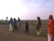 Refugees in Kenya walk along the road.